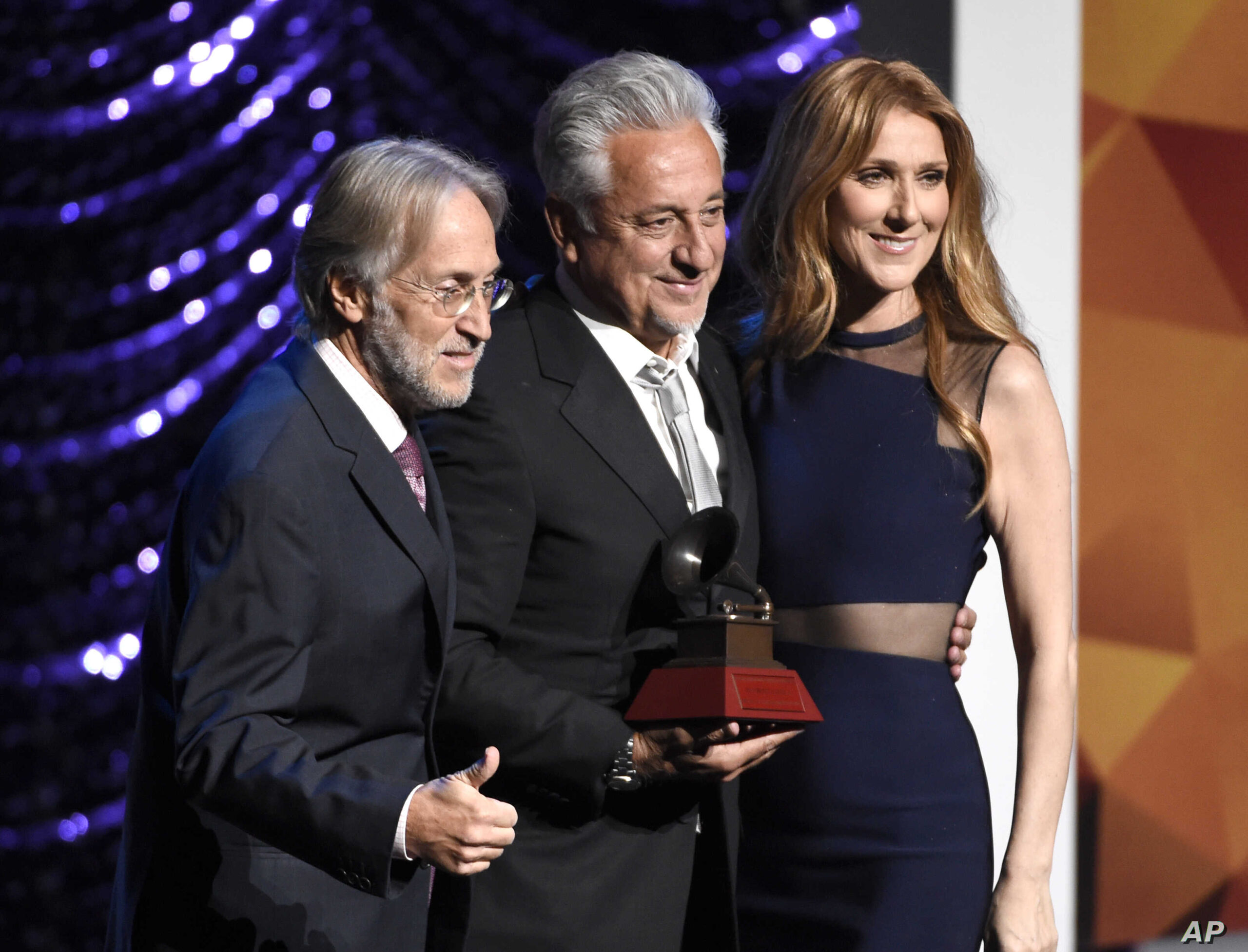 Neil Portnow, president and CEO of the Recording Academy, from left, Trustees Award recipient Humberto Gatica and Celine Dion pose on stage at the Lifetime Achievement and Trustees Awards presentation at the Ka Theater in the MGM Grand Hotel on Wednesday, Nov. 18, 2015, in Las Vegas. (Photo by Chris Pizzello/Invision/AP)