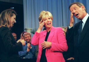 """Joan Lunden, center, and Charles Gibson, right, wipe tears from their eyes as Celine Dion, left, serenades her with """"Because you loved me"""". (AP Photo/Michael Schmelling)"""