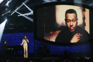 Céline Dion is accompanied by Richard Marx on the piano in a tribute to Luther Vandross (on screen). (© AP Photo/Kevork Djansezian)