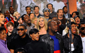 In this handout photo provided by WATW, singers Céline Dion, Justin Bieber, Usher, Katharine McPhee, will.i.am, Toni Braxton, Barbra Streisand, LL Cool J, Harry Connick Jr., Wyclef Jean, Vince Vaughn, Jeff Bridges, Natalie Cole and others perform at (© Handout/Getty Images North America)